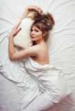 Pretty blond woman laying in bed Stock Photos