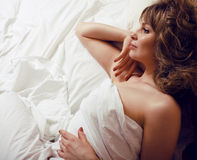 Pretty blond woman laying in bed Stock Image