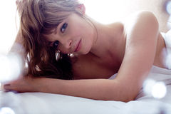 Pretty blond woman laying in bed Royalty Free Stock Photos