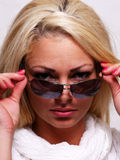Pretty blond woman looking over her glasses. Royalty Free Stock Images