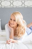 Pretty Blond Woman Lying in Prone on Bed Stock Photos