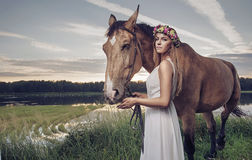 Pretty blond woman posing with a stallion Royalty Free Stock Image