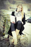 Pretty blond woman reading a book outdoors Stock Photography