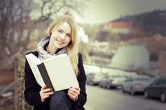Pretty blond woman reading a book outdoors Stock Photos