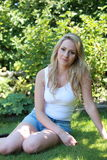 Pretty blond woman relaxing in her garden Royalty Free Stock Image
