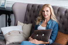 Pretty blond woman sitting on grey couch Stock Photos