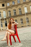 Pretty Blond Woman Sitting on Red Chair Stock Image
