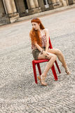 Pretty Blond Woman Sitting on Red Chair Royalty Free Stock Image