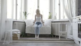Pretty blond woman sitting on white small couch at home in front of the window. Action. Attractive girl in white tank royalty free stock images