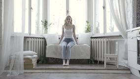 Pretty blond woman sitting on white small couch at home in front of the window. Action. Attractive girl in white tank. Pretty blond woman sitting on white small stock video