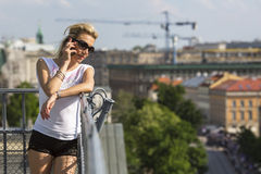 Pretty  blond woman talking on mobile phone outdoors in the city. Stock Image