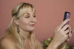 A pretty blond woman texting on her pink cell phone Stock Photos