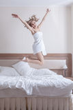 Pretty blond woman in towels jump on big bed Stock Photography