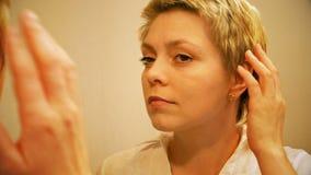 Pretty blond woman wears earrings and smartens up stock video