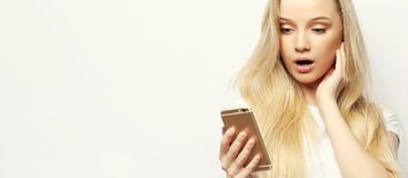 Pretty Blond Woman With Long Hair Holds Modern Smart Phone, Recieves Unexpcted Message From Friend, Reads Reminder Stock Photo