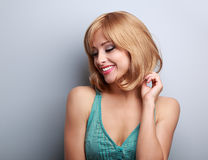 Pretty blond young woman with short hairstyle looking down. Natural smile. Closeup portrait royalty free stock image