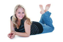 Pretty Blonde. Blue eyed, barefoot woman relaxing on the floor on a white backdrop, not isolated Stock Image