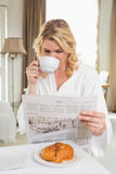 Pretty blonde in bathrobe drinking coffee and reading newspaper Stock Photos