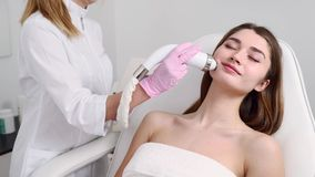 Pretty blonde beautician doctor doing rf-lifting procedure for woman laying in a beauty salon. Hardware cosmetology. Pretty blonde beautician doctor doing rf stock video
