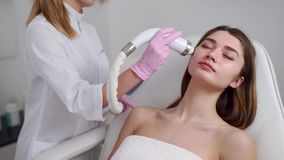 Pretty blonde beautician doctor doing rf-lifting procedure for woman laying in a beauty salon. Hardware cosmetology. Pretty blonde beautician doctor doing rf stock footage