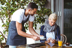 Pretty blonde being served a cup of coffee. At the cafe Royalty Free Stock Image