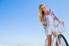 Pretty blonde on a bike ride at the beach smiling at camera Royalty Free Stock Photos