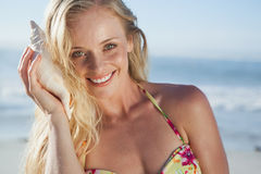 Pretty blonde in bikini listening to conch on the beach Stock Photo