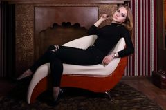 Pretty blonde in black poses on ottoman. In studio with decorative fireplace Stock Photo