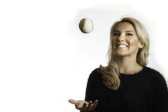 Pretty Blonde Black Shirt Tossing Up Baseball Isolated White Background. A pretty, latina, blonde  in a black scarf tossing up and catching a baseball while Stock Photo