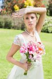 Pretty blonde bride holding arm to forehead Royalty Free Stock Image