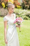 Pretty blonde bride holding lily bouquet Royalty Free Stock Photo