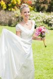 Pretty blonde bride holding lily bouquet and her dress Royalty Free Stock Image