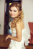 Pretty blonde bride with long hair smiles looking over her shoul Stock Photography