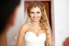 Pretty blonde bride with long hair smiles looking over her shoul. Der stock photos