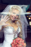Pretty blonde bride looking through the window Stock Photography