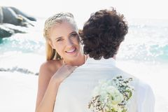 Pretty blonde bride smiling at camera while hugging husband stock photography