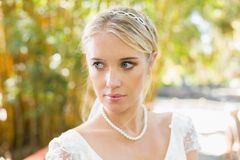 Pretty blonde bride standing on a bridge looking away Stock Photo