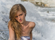 Pretty blonde brunette girl in front of a river waterfall Royalty Free Stock Images