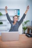 Pretty blonde businesswoman gesturing victory Stock Photos