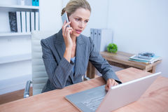 Pretty blonde businesswoman phoning and using her laptop. At the office Royalty Free Stock Photo