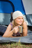 Pretty blonde camper smiling and lying in tent Royalty Free Stock Image