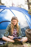 Pretty blonde camper using tablet and sitting in tent Royalty Free Stock Photo