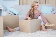 Pretty blonde on carpet with boxes holding book Stock Photography