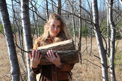 Pretty blonde carrying firewood Stock Image