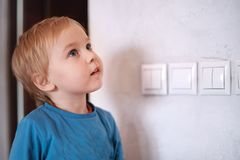 Pretty blonde caucasian baby boy looks up near to the wall with light-switch. Big blue eyes, attentive expression, close up portra royalty free stock photography