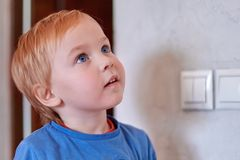 Pretty blonde caucasian baby boy looks up near to the wall with light-switch. Big blue eyes, attentive expression, close up portra stock photos