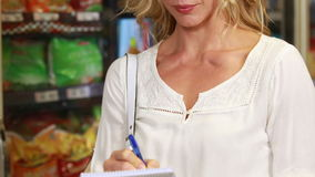 Pretty blonde checking grocery list. In grocery store stock video