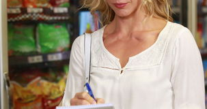 Pretty blonde checking grocery list. In grocery store stock footage