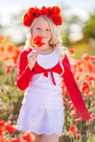 Pretty blonde child girl in spring field with poppies Royalty Free Stock Photos