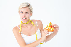 Pretty blonde choosing between eating pizza or not Stock Photos